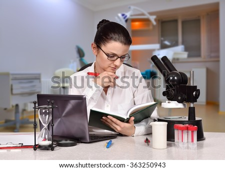 young female scientist reading a book sitting in laboratory - stock photo