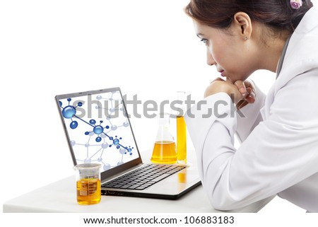 Young female scientist watching a molecule reaction on the screen of laptop computer - stock photo