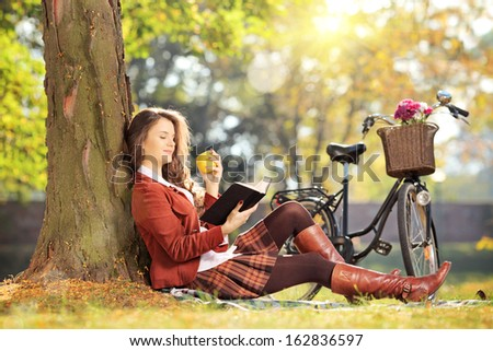 Young female seated on a grass in park reading a book and eating apple, on a sunny day - stock photo
