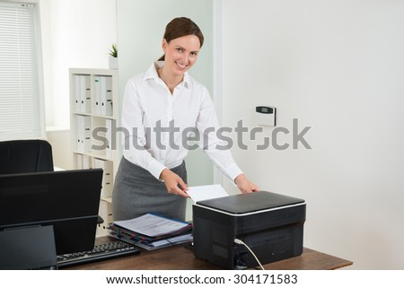 Young Female Secretary Inserting Paper In Printer At Desk - stock photo