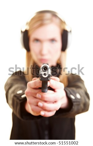 Young female shooter with pistol and ear protection - stock photo