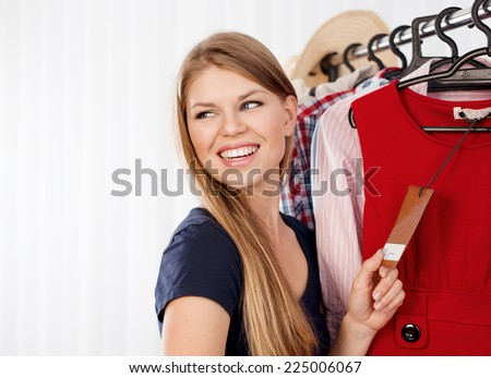 Young female shopper holding price tag of new dress in retail store. Portrait of attractive joyful shopping woman dreaming of buying clothes.   - stock photo