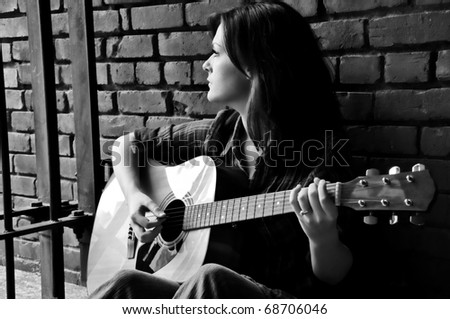 Young female sitting against brick wall and playing guitar while looking through bars. - stock photo