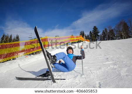 Young female skier in blue ski suit after the fall on mountain slope against ski lift and winter mountains background. Ski resort. Winter sports concept. - stock photo