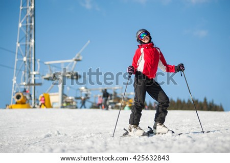 Young female skier wearing helmet, red jacket and ski goggles standing with skis on mountain top at a winter resort in sunny day with ski lifts and blue sky in background. - stock photo