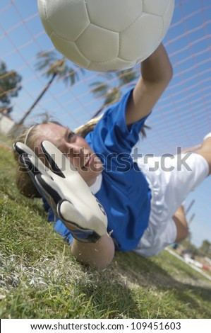 Young female soccer goalkeeper diving to block a goal attempt - stock photo