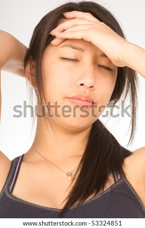 Young female squeezing her head apparently having headache - stock photo