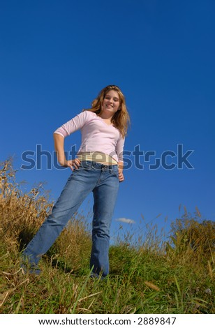 Young female standing on a hill against blue sky - stock photo