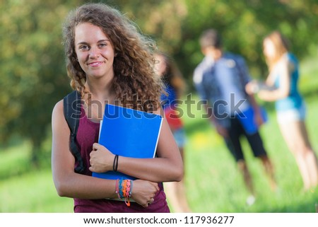 Young Female Student at Park with Other Friends - stock photo