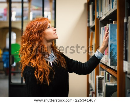 Young female student consulting book from shelf in public library.  - stock photo