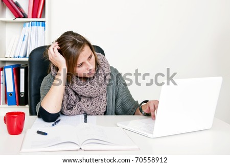 Young female student doing internet research whilst studying her textbooks behind her desk - stock photo