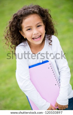 Young female student holding notebooks and looking happy - stock photo