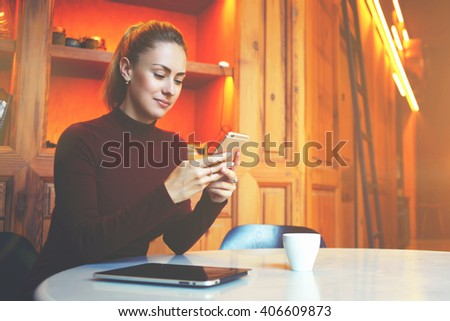 Young female student is chatting on mobile phone with friend while sitting in modern library interior, gorgeous Caucasian woman using cell telephone while rest in coffee shop during winter holidays - stock photo