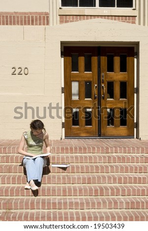 Young female student is reading on the steps in the college campus - stock photo