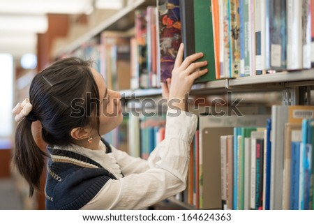 Young female student putting a green book back onto a bookshelf in library - stock photo