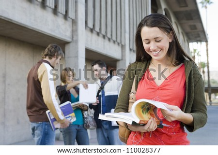 Young female student reading book - stock photo