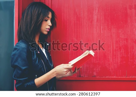 Young female student reading interesting book while standing in the city on red wall background with copy space for your text message, afro american woman read literature while standing outdoors - stock photo