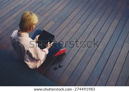 Young female student relaxing in a university recreation hall using touch pad, freelancer girl working on her digital tablet with big copy space, hipster woman using touchscreen device, filtered image - stock photo