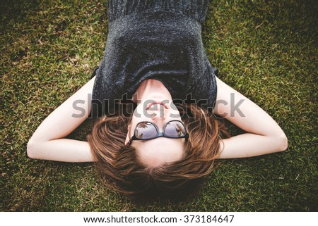 Young female student relaxing on the green grass in Central Park, New York  - stock photo