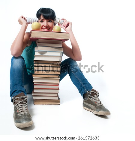 Young female student sitting with books, energy saving light bulbs and apples - stock photo