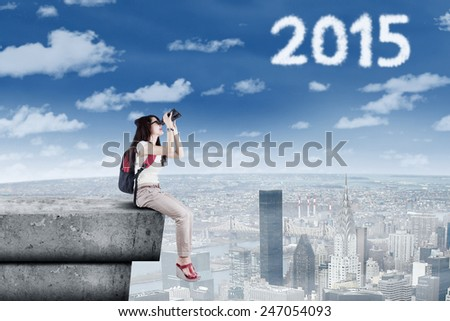 Young female student using binoculars to see numbers 2015 while sitting at building roof - stock photo