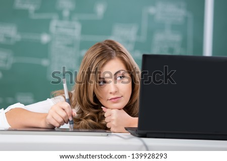 young female student using graphic tablet against chalkboard in classroom - stock photo