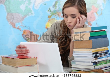 young female student with laptop surrounded by books - stock photo