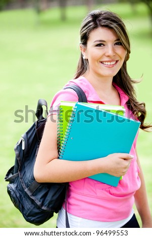 Young female student with notebooks looking happy - stock photo