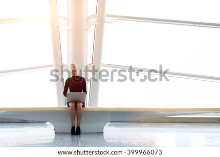 Young female successful freelancer is using portable laptop computer for distance work during her trip in China, while is sitting in co-working space in skyscraper building background with copy space - stock photo