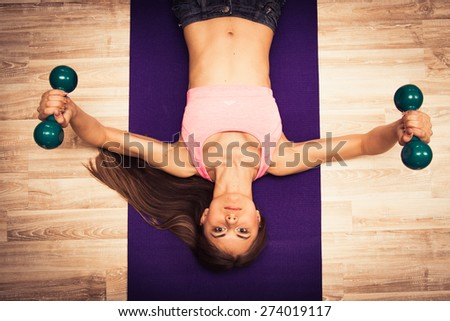 Young female swinging muscles with a dumbbells - stock photo