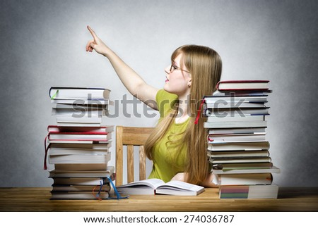 Young female teacher at a table with books pointing the finger back - stock photo