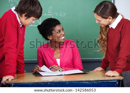 Young female teacher discussing with students at desk in classroom - stock photo