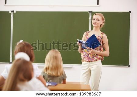 Young female teacher standing near blackboard at school - stock photo