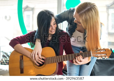 Young female teaching her girlfriend to play guitar. - stock photo