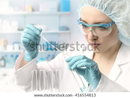 Young female tech or scientist loads liquid sample into test tube with plastic pipette. Shallow DOF, focus on the hand with the tube. - stock photo
