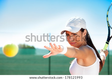 young female tennis player ready to hit ball - stock photo