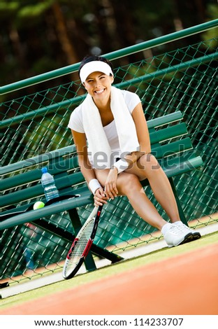 Young female tennis player rests with bottle of water on the bench at the tennis court - stock photo