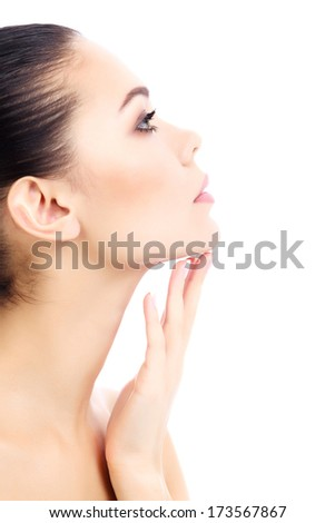 Young female touches her neck, white background, copyspace  - stock photo