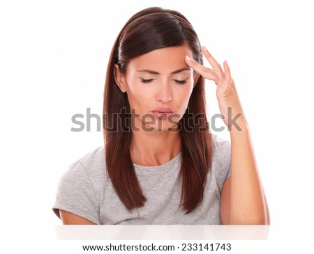 Young female touching her forehead suffering a big headache in white background - stock photo