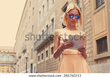 Young female tourist checking out the sights while reading a map, gorgeous woman holding a map while touring abroad, stylish hipster studying a map while standing in urban setting in summer, filter - stock photo