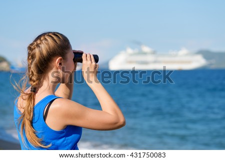 Young female tourist looking through binoculars at white cruise ship (liner) and enjoying beautiful sea view. Woman wearing blue dress. Her hair braided in French plait. Outdoor portrait in summer. - stock photo