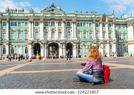 Young female tourist resting on the square in front of the Winter Palace in St. Petersburg, Russia - stock photo