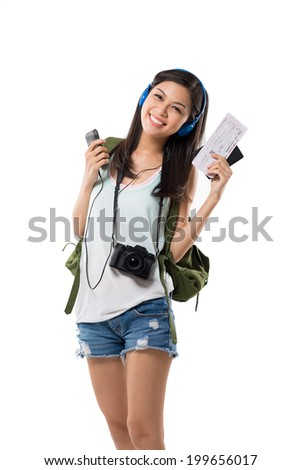 Young female tourist with boarding pass listening to the music in the headphones - stock photo