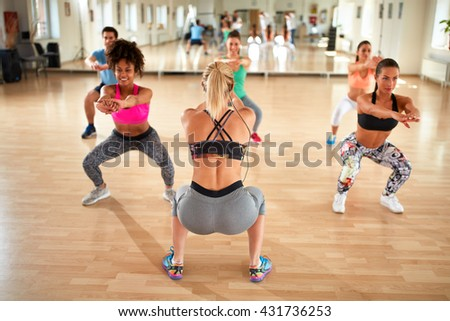 Young female trainer doing squat exercise with fitness group - stock photo