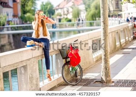 Young female traveler enjoying the music sitting with bicycle near the river in Ljubljana city. Traveling in Slovenia - stock photo