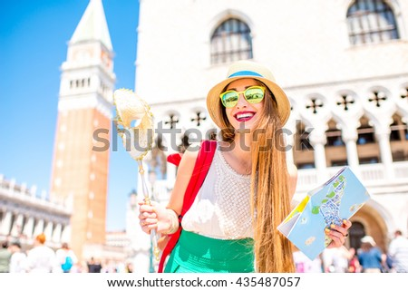 Young female traveler having fun with carnaval mask and tourist map on San Marco square in Venice. Happy traveling in Venice - stock photo