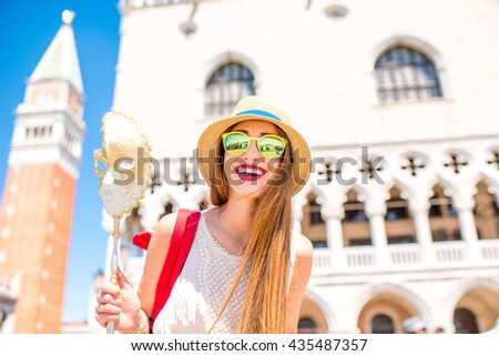 Young female traveler having fun with carnaval mask standing on San Marco square in Venice. Happy traveling in Venice - stock photo