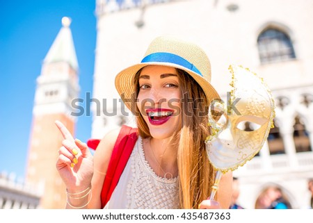 Young female traveler pointing with finger on San Marco tower holding carnaval mask in Venice. Happy traveling in Venice - stock photo