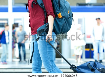 Young female traveler walking with backpack and pulling bag - stock photo
