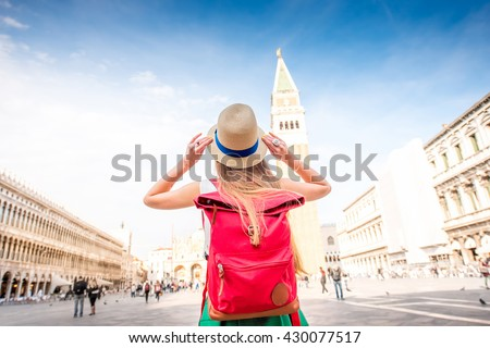 Young female traveler with hat and backpack standing on San Marco square with tower and basilica on the background in Venice. Back view - stock photo